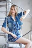 Frau in der Jeansjacke, die auf Treppe sitzt Stockbild