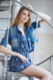 Frau in der Jeansjacke, die auf Treppe sitzt Lizenzfreie Stockfotos