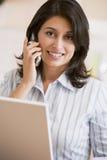 Frau in der Küche mit dem Laptop- und Mobiltelefonlächeln Lizenzfreie Stockbilder