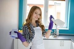 Frau in der Küche mit einem Lappen und einer Sprühflasche Lizenzfreies Stockfoto