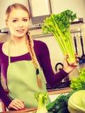 Frau in der Küche mit grünem Gemüse Lizenzfreie Stockbilder