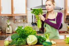 Frau in der Küche mit grünem Gemüse Lizenzfreies Stockbild