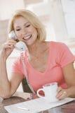 Frau in der Küche mit Kaffee unter Verwendung des Telefons Lizenzfreie Stockfotos