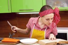 Frau in der Küche mit Messerrezeptbuch Lizenzfreie Stockfotos