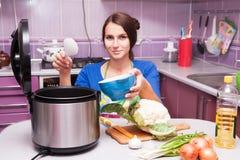 Frau in der Küche und im multivarka Stockbilder