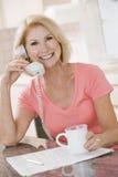 Frau in der Küche unter Verwendung des Telefons und des Lächelns Lizenzfreie Stockfotografie