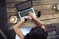 Frau an der Kaffeestube Zeit auf smartwatch überprüfend Lizenzfreie Stockfotografie
