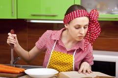 Frau in der Küche mit Messerrezeptbuch Stockbilder