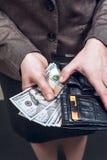 Frau in der Klage mit dem ledernen Geldbeutel voll vom Geld Stockbild