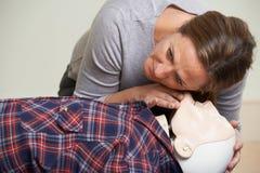 Frau in der Klasse der ersten Hilfe, die Fluglinie auf CPR-Attrappe überprüft Lizenzfreie Stockbilder
