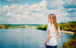 Frau an der Klippe über dem Fluss Lizenzfreies Stockfoto