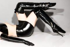 Frau in der Latexkleidung, die ihre Stiefel zeigt Stockbild