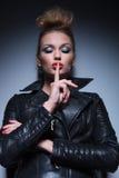 Frau in der Lederjacke, die das ruhige Zeichen macht Stockfotografie