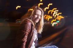 Frau in der Lederjacke und in Blue Jeans, die auf Schienen spielen lizenzfreie stockfotografie