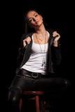 Frau in der ledernen Kleidung zieht ihren Kragen und sitzt Stockfotografie