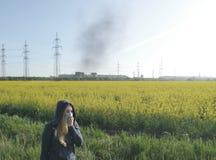 Frau in der medizinischen Maske vor dem hintergrund der Anlage Das Konzept der Umweltverschmutzung, ?kologie lizenzfreie stockfotografie