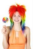 Frau in der mehrfarbigen Perücke mit großem Lutscher Lizenzfreie Stockfotografie
