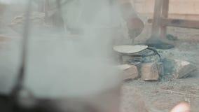Frau in der mittelalterlichen Kleidung, die Pfannkuchen an der Stange brät stock video footage