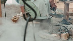 Frau in der mittelalterlichen Kleidung, die Pfannkuchen an der Stange brät stock footage