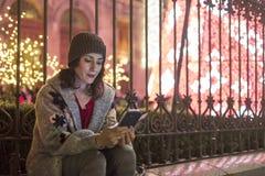 Frau in der Nachtweihnachtsszene, die Smartphoneschirm schaut Lizenzfreie Stockfotografie