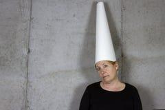 Frau in der Narrenkappe, leere Wand Stockfoto
