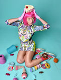 Frau in der Pinkparteiperücke, die gefälschten Süßigkeitskuchen auf Kopf hält und Stockbild