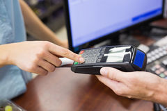 Frau an der Registrierkasse, die mit Kreditkarte zahlt Stockfotos