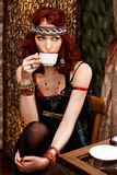 Frau in der Retro- Kleidung trinkt Kaffee im Kaffeestab Lizenzfreie Stockfotografie