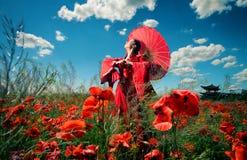 Frau in der roten Kleidung auf dem Mohnblumengebiet Stockfoto