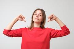 Frau in der roten Strickjacke stolz und überzeugt, Finger zeigend, Beispiel, um zu folgen lizenzfreies stockfoto