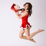 Frau in der roten Weihnachtskostümfliege mit Geschenk Lizenzfreies Stockfoto