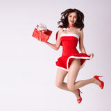Frau in der roten Weihnachtskostümfliege mit Geschenk Lizenzfreie Stockfotos