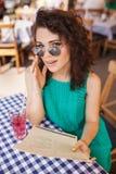 Frau in der runden Sonnenbrille mit dem Cocktail, das Bestellung am Café macht Stockbilder