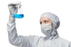 Frau in der Schutzkleidung, die eine blaue Flüssigkeit auf einem weißen Hintergrund betrachtet Stockfotografie
