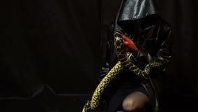 Frau in der schwarzen Haube mit Schlange stock video footage