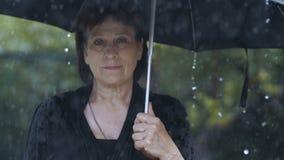 Frau an der schwarzen Kleidung unter Regenschirm am Regen stock video