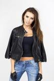 Frau in der schwarzen Lederjacke und Handschuhe, die an aufwerfen Lizenzfreies Stockfoto