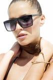 Frau in der schwarzen Sonnenbrille und im Badeanzug, die goldenes Armband mit dem Haar wirft trägt oben, auf weißem Hintergrund a Lizenzfreie Stockfotos
