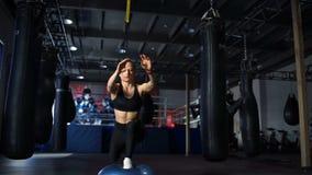 Frau in der schwarzen Sportkleidung, die Laufleinen auf dem Bosu und dem TRX in der Turnhalle tut stock footage