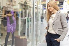 Frau in der shoping Straße, die Fenster betrachtet Stockfotos
