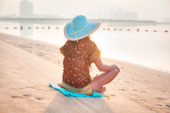 Frau an der Sonnenaufgangmeditation auf dem Strand Stockbilder