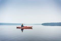 Frau in der Sonnenbrille den See vom roten Kajak genießend Stockbilder
