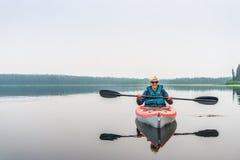 Frau in der Sonnenbrille den See vom roten Kajak genießend Stockfotos
