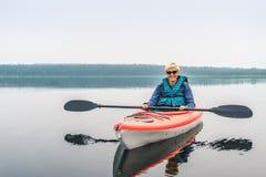 Frau in der Sonnenbrille den See vom roten Kajak genießend Stockfoto