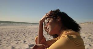 Frau in der Sonnenbrille, die auf dem Strand 4k sich entspannt stock footage