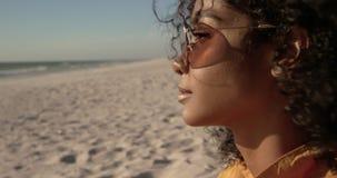 Frau in der Sonnenbrille, die auf dem Strand 4k sich entspannt stock video footage