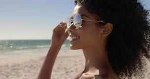Frau in der Sonnenbrille, die auf dem Strand 4k steht stock footage