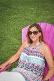 Frau in der Sonnenbrille, die draußen auf rosa Adirondack-Stuhl sitzt Lizenzfreie Stockfotos