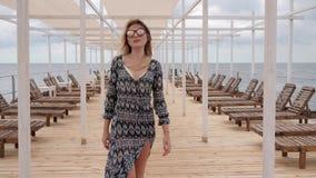Frau in der Sonnenbrille geht entlang Anlegestelle nahe Meer, langhaariges Mädchen, beim sich Entwickeln kleidet auf Ufergegend,  stock video footage