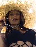 Frau in der Sonnenbrille und im schwarzen stilvollen Badeanzug des Hutes Stockfotos